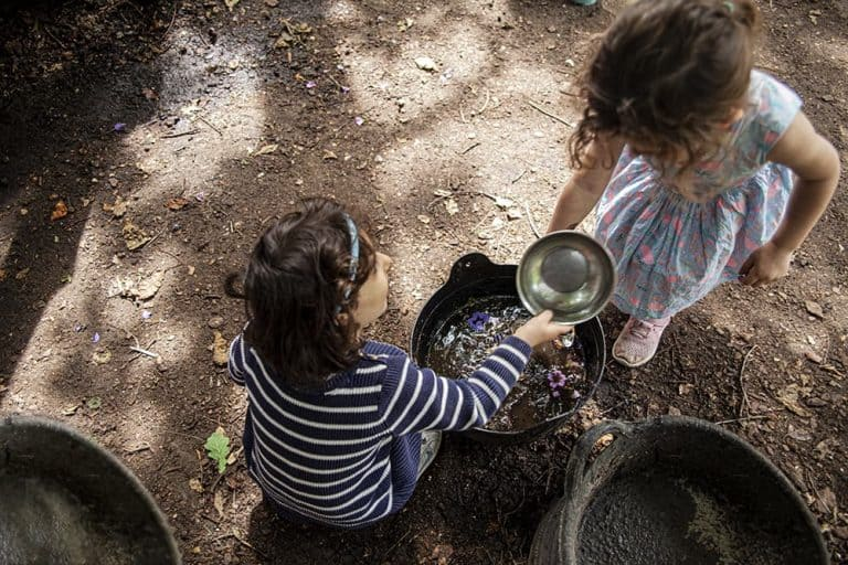 Two children making a mixture in a pot in the Mud Garden