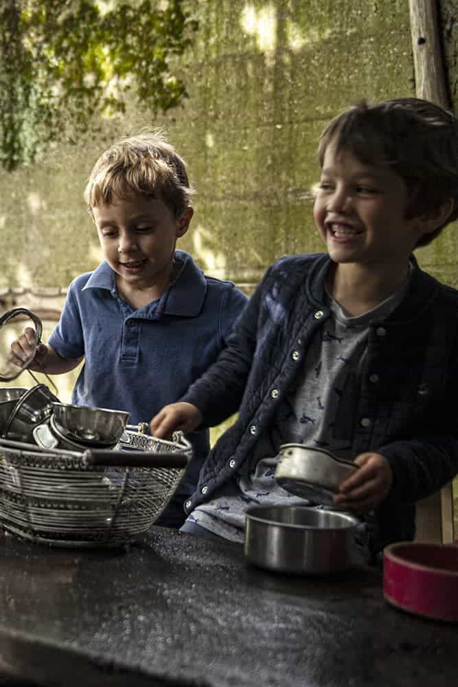 Two boys playing with kitchen utensils in the Mud Garden