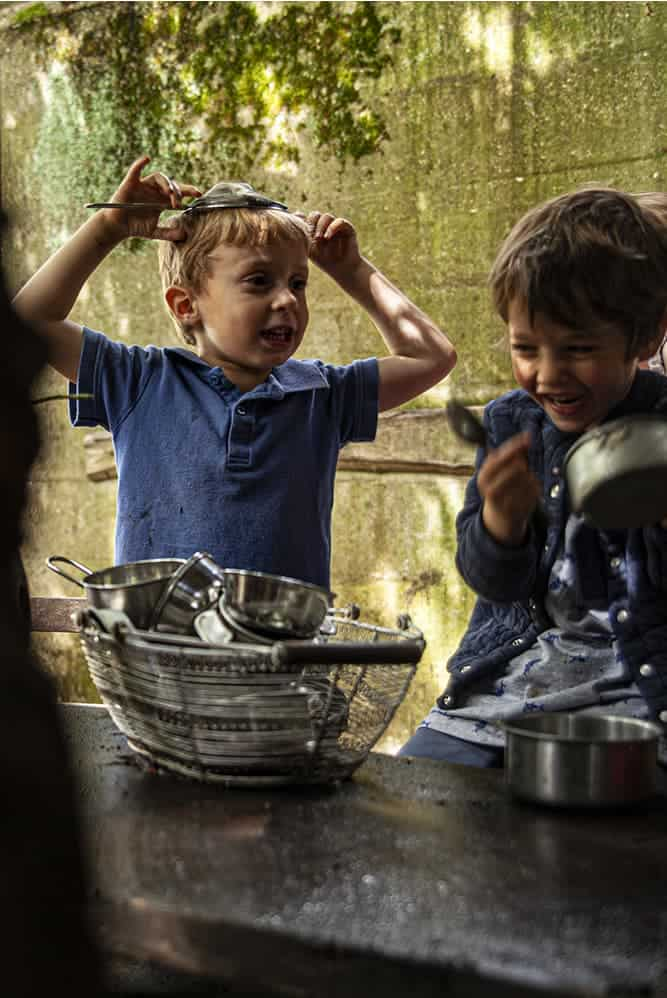 Two boys playing with kitchen with utensils as instruments in the Mud Garden