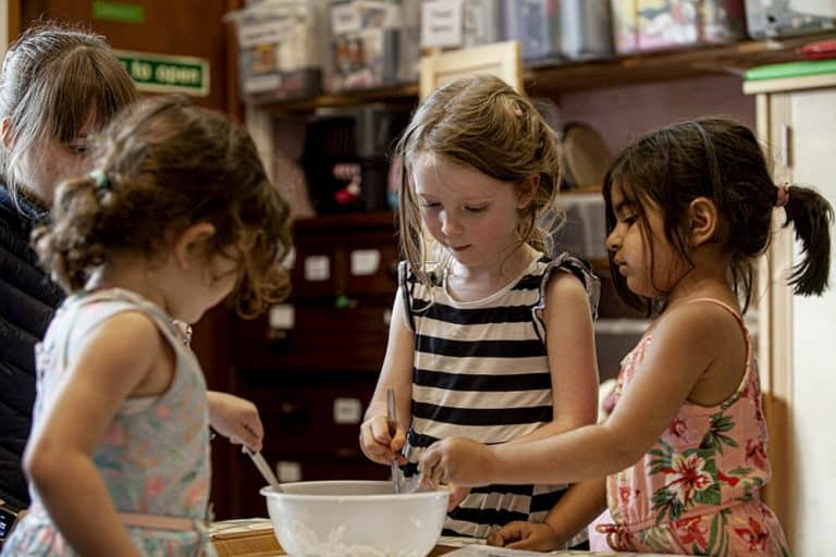 Three girls mixing  the sourdough bread mixture in a bowl