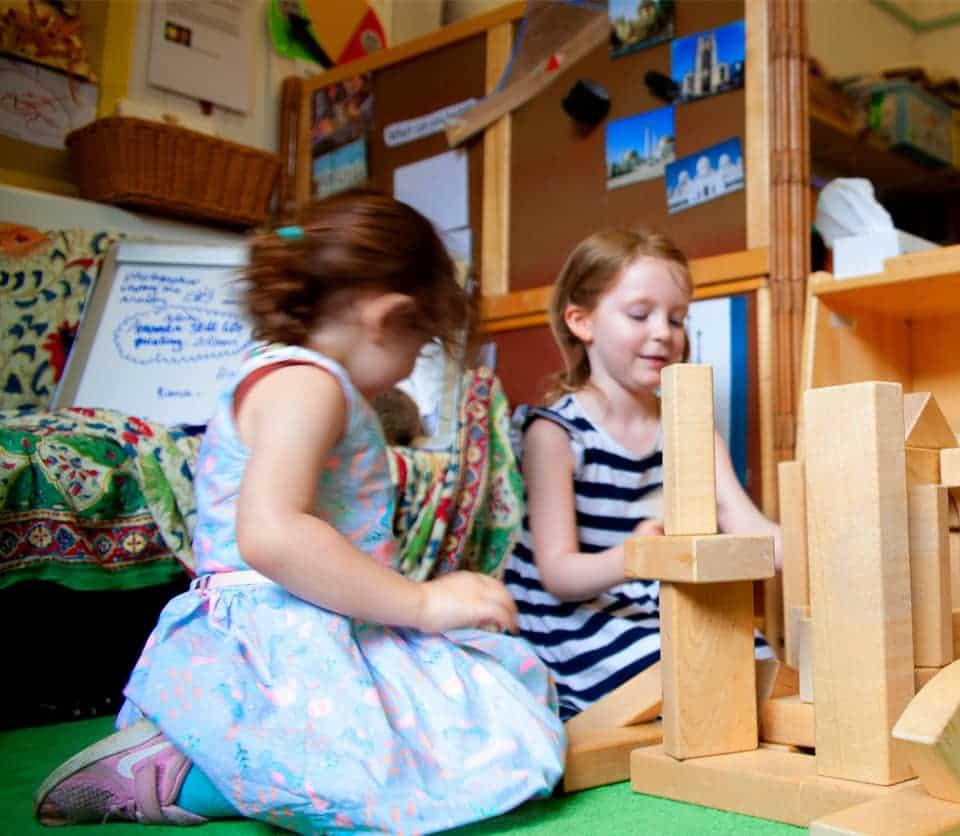 Two children play with wooden building blocks