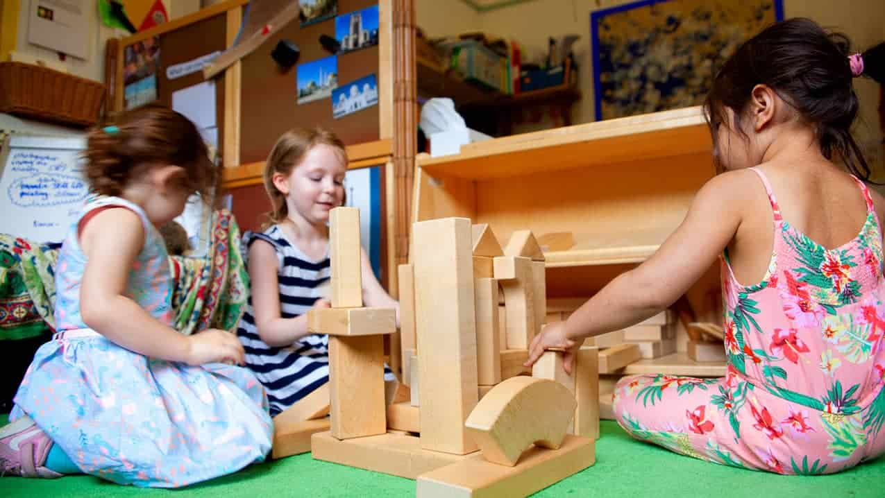 Three children play with wooden building blocks