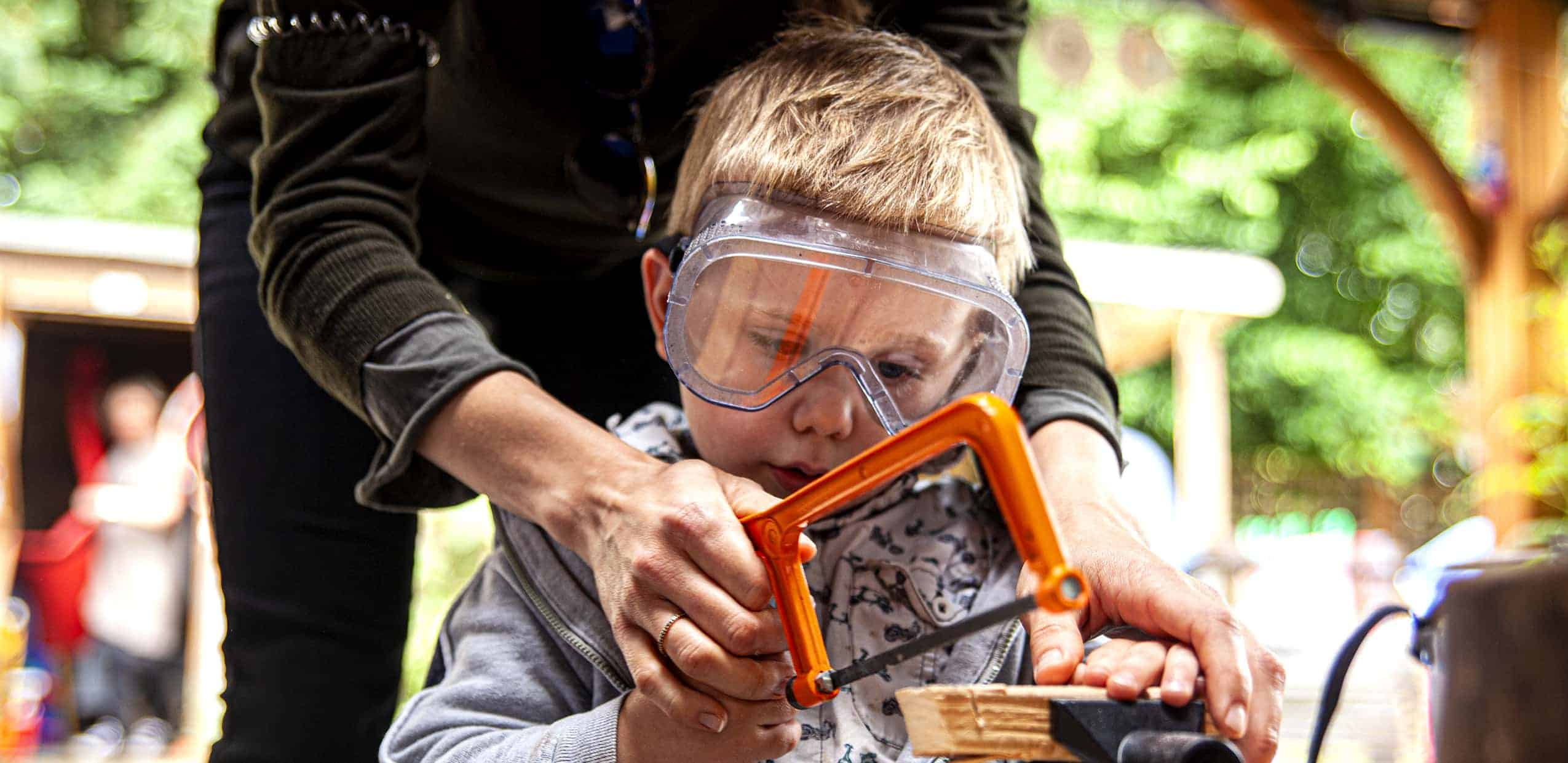 Close up of a boy being helped to saw wood in a vice