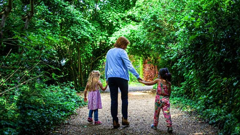 An adult and two children walking down Millington Road Nursery School leafy lane entrance