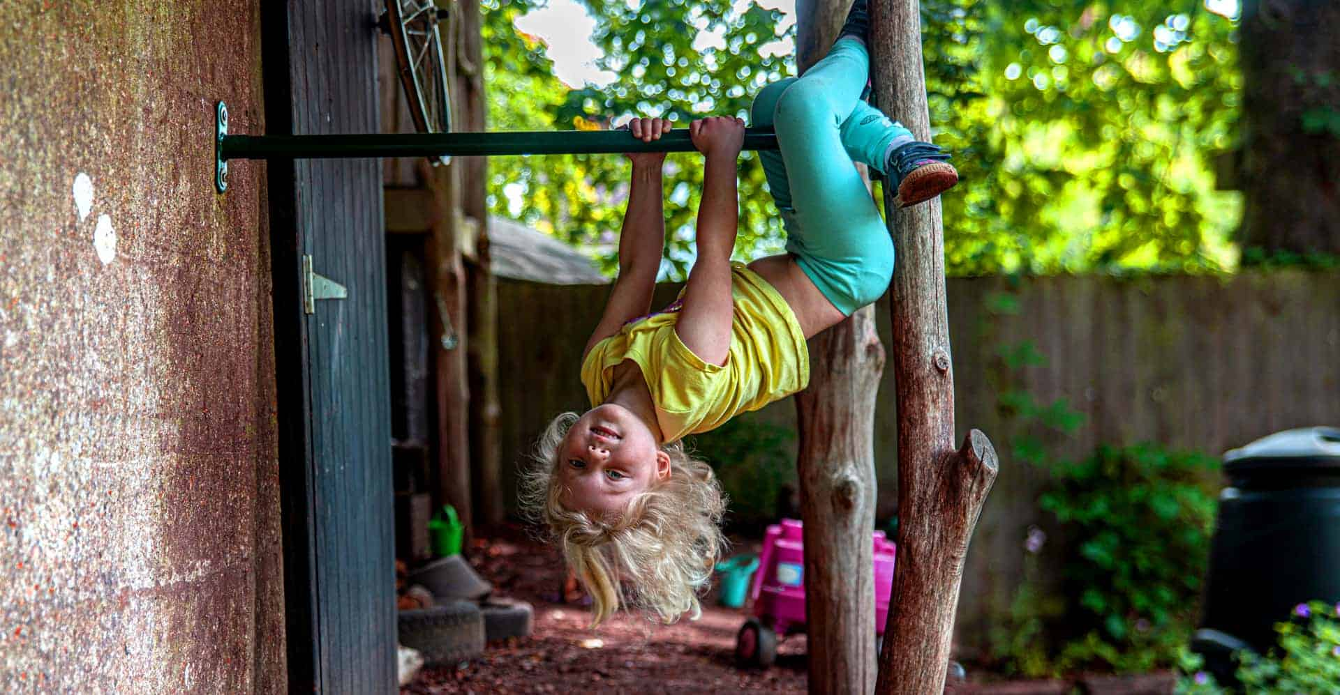 Hanging upside down outside on a climbing bar