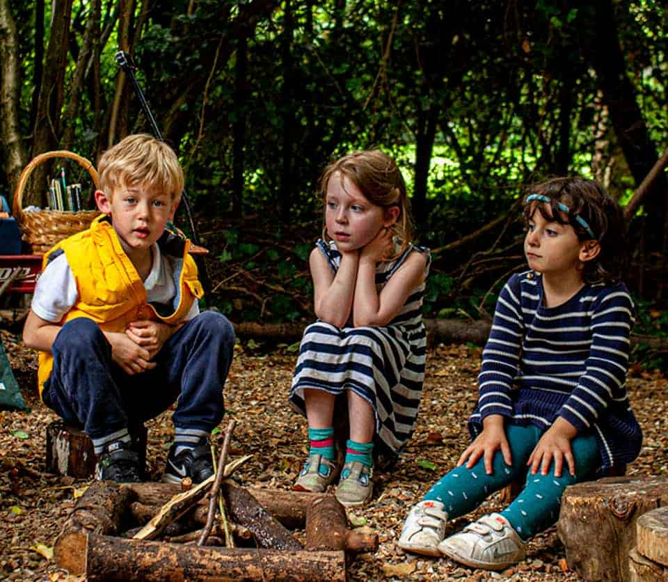 Three children sitting round unlit wood pile campfire