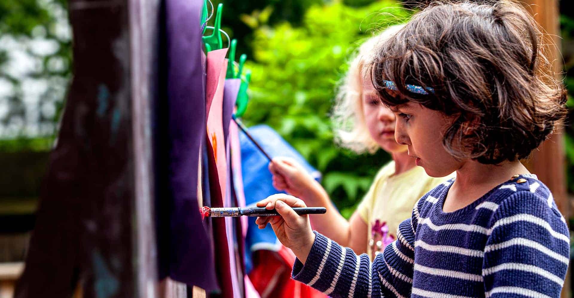Two children painting outside in the nursery's garden