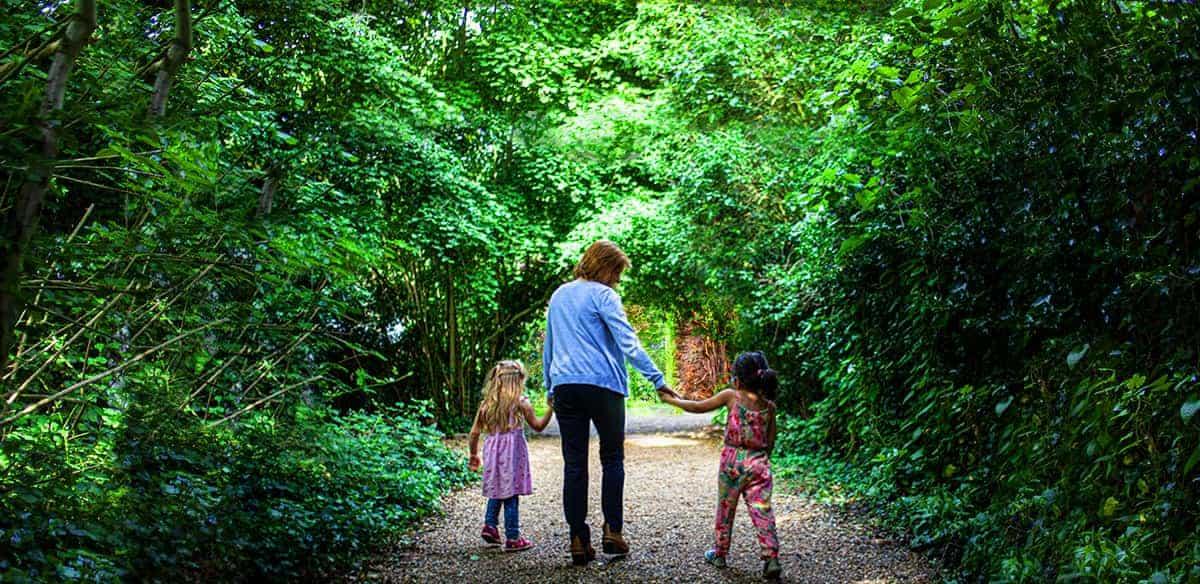 An adult with two children walking down Millington Road Nursery School leafy lane entrance